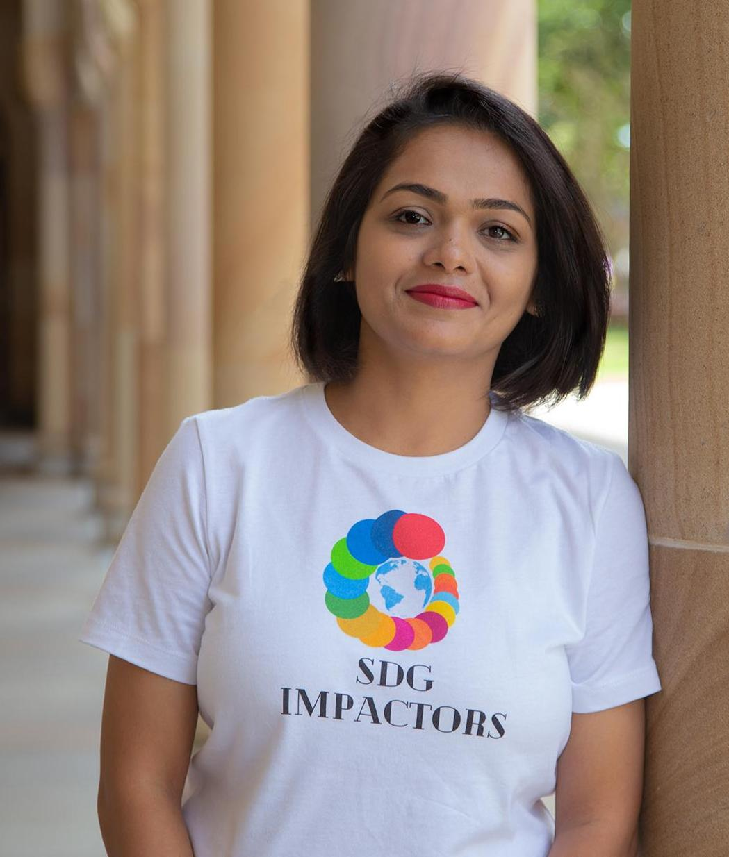 Runali wearing t-shirt with SDG colours representing the 17 UN goals