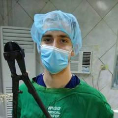 student hamming it up in a surgical room - with bolt cutters.