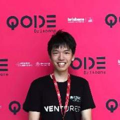 Ocean wearing a black t-shirt with VENTURES written on the front. He's standing in front of the QODE Brisbane pink wall advertising the QODE event