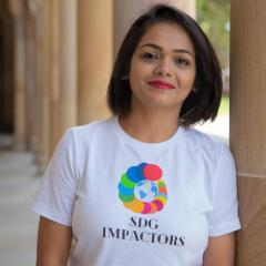 Runali wearing her t-shirt with circles shaped like a shell with the 17 sustainable development goals represented in differing colours.