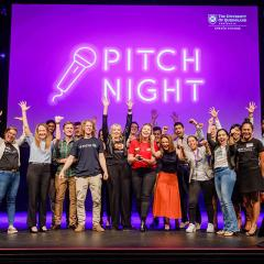 Pitch Night group shot with everyone's hands in the air - very happy vibe. Words 'PITCH NIGHT' in neon behind them.