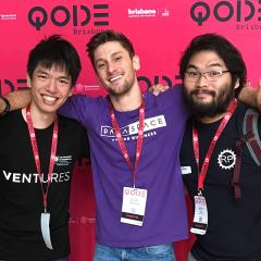 Ocean with two other young men at QODE exhibition behind QODE media wall