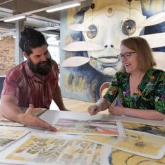 Street artist and UQ AI researcher collaborating at table