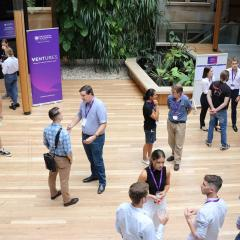 People standing and networking in event space