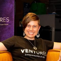 Sam Jockel sitting on an orange couch with the purple Ventures sign behind her