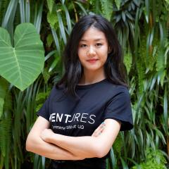 Rachel Huang in front of green wall (leafy plants) - she's wearing the Ventures entrepreneurship at UQ tshirt